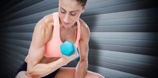 Imagen compuesta de la mujer fuerte que hace el rizo del bíceps con pesa de gimnasia azul Imagenes de archivo