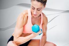 Imagen compuesta de la mujer fuerte que hace el rizo del bíceps con pesa de gimnasia azul Fotografía de archivo libre de regalías
