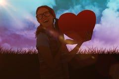 Imagen compuesta de la mujer geeky del inconformista que sostiene la tarjeta del corazón Foto de archivo libre de regalías