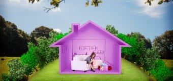 Imagen compuesta de la mujer linda que se sienta en el sofá que saca sus zapatos Fotografía de archivo libre de regalías