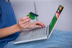 Imagen compuesta de la mujer que hace compras en línea con el ordenador portátil y la tarjeta de crédito Imagenes de archivo