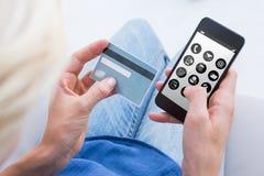 Imagen compuesta de la mujer que hace compras en línea con su teléfono móvil Fotos de archivo libres de regalías