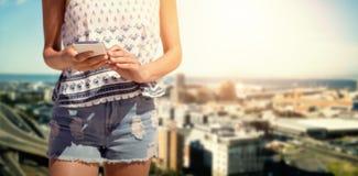 Imagen compuesta de la mujer que manda un SMS en un teléfono móvil Fotos de archivo libres de regalías