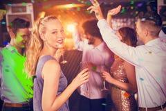 Imagen compuesta de la mujer que sostiene el vidrio de champán mientras que baila con los amigos Imágenes de archivo libres de regalías