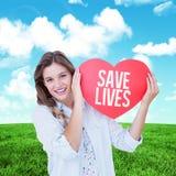 Imagen compuesta de la mujer que sostiene la tarjeta del corazón Imagen de archivo libre de regalías