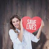 Imagen compuesta de la mujer que sostiene la tarjeta del corazón Fotos de archivo libres de regalías