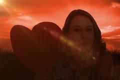 Imagen compuesta de la mujer que sostiene la tarjeta del corazón y que sopla beso Foto de archivo libre de regalías