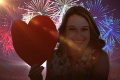 Imagen compuesta de la mujer que sostiene la tarjeta del corazón y que sopla beso Imagen de archivo libre de regalías
