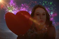 Imagen compuesta de la mujer que sostiene la tarjeta del corazón y que sopla beso Fotografía de archivo libre de regalías