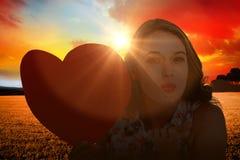 Imagen compuesta de la mujer que sostiene la tarjeta del corazón y que sopla beso Fotos de archivo