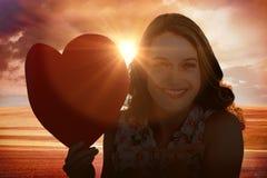 Imagen compuesta de la mujer que sostiene la tarjeta del corazón y que sopla beso Imágenes de archivo libres de regalías