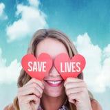 Imagen compuesta de la mujer que sostiene tarjetas del corazón Fotos de archivo