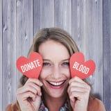 Imagen compuesta de la mujer que sostiene tarjetas del corazón Imagenes de archivo