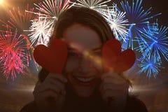 Imagen compuesta de la mujer que sostiene tarjetas del corazón Foto de archivo libre de regalías