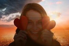 Imagen compuesta de la mujer que sostiene tarjetas del corazón Imágenes de archivo libres de regalías