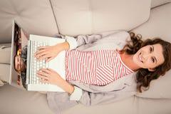 Imagen compuesta de la mujer que usa el ordenador portátil mientras que miente en el sofá en casa Fotos de archivo libres de regalías