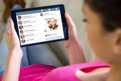 Imagen compuesta de la mujer que usa la tableta en casa Imágenes de archivo libres de regalías