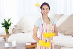 Imagen compuesta de la mujer sonriente con una escoba en su hombro Imagen de archivo libre de regalías