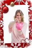 Imagen compuesta de la mujer sonriente que pone el dinero en una hucha que ella está sosteniendo Fotografía de archivo libre de regalías