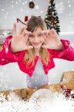 Imagen compuesta de la niña festiva que hace las galletas de la Navidad Imagen de archivo libre de regalías