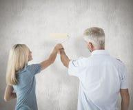 Imagen compuesta de la pared feliz de la pintura de los pares con el rodillo Fotografía de archivo