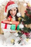 Imagen compuesta de la pila que se sostiene morena festiva de regalos cerca de un árbol de navidad Imagenes de archivo