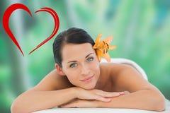 Imagen compuesta de la relajación morena hermosa en la tabla del masaje que sonríe en la cámara Foto de archivo libre de regalías