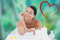 Imagen compuesta de la relajación morena hermosa en la tabla del masaje que sonríe en la cámara Fotografía de archivo