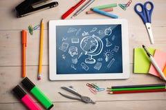 Imagen compuesta de la tableta digital en el escritorio de los estudiantes Imágenes de archivo libres de regalías