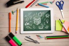 Imagen compuesta de la tableta digital en el escritorio de los estudiantes Imagen de archivo
