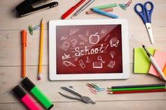 Imagen compuesta de la tableta digital en el escritorio de los estudiantes Fotos de archivo libres de regalías