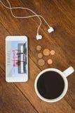 Imagen compuesta de la vista de un smartphone blanco con una taza de café Imágenes de archivo libres de regalías