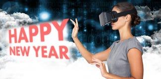 Imagen compuesta de la vista lateral de la mujer joven que gesticula mientras que usa los vidrios video virtuales Foto de archivo libre de regalías