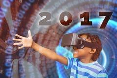 Imagen compuesta de la vista lateral del niño pequeño que sostiene los vidrios virtuales en un fondo blanco Imagenes de archivo