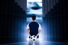 Imagen compuesta de la vista posterior del deportista que lleva a cabo fútbol en su 3d trasero Imagen de archivo libre de regalías