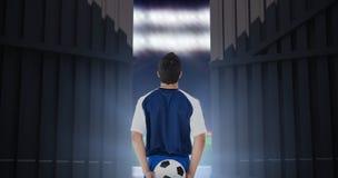 Imagen compuesta de la vista posterior del futbolista que sostiene la bola en 3d trasero Fotos de archivo