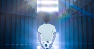 Imagen compuesta de la vista posterior del futbolista que sostiene la bola en el 3d trasero Imagen de archivo