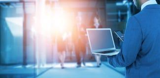 Imagen compuesta de la vista posterior del hombre de negocios usando el ordenador portátil y el teléfono móvil fotos de archivo libres de regalías