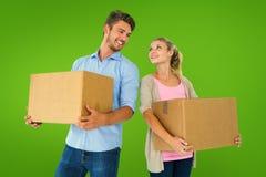 Imagen compuesta de las cajas móviles que llevan de los pares jovenes atractivos Imagen de archivo libre de regalías
