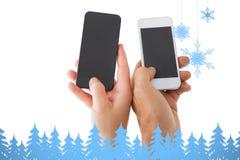 Imagen compuesta de las manos de los pares que sostienen smartphones Imágenes de archivo libres de regalías