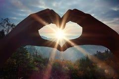 Imagen compuesta de las manos que hacen forma del corazón en la playa fotografía de archivo libre de regalías