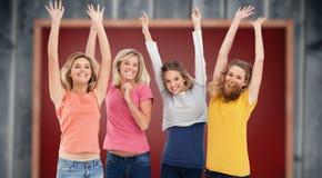Imagen compuesta de las muchachas de celebración sonrientes que saltan para arriba Fotos de archivo libres de regalías