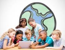 Imagen compuesta de los alumnos lindos que usan la tableta en biblioteca Imagenes de archivo
