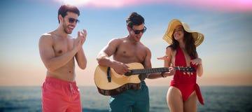 Imagen compuesta de los amigos que juegan música en traje de baño Foto de archivo libre de regalías