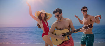 Imagen compuesta de los amigos que juegan música en traje de baño Imagen de archivo
