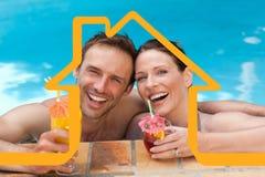 Imagen compuesta de los cócteles de consumición de los pares hermosos en la piscina Fotos de archivo libres de regalías