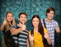 Imagen compuesta de los estudiantes felices que gesticulan los pulgares para arriba en el pasillo de la universidad Imagenes de archivo