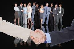 Imagen compuesta de los hombres de negocios sonrientes que sacuden las manos Imagen de archivo