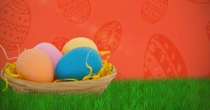 Imagen compuesta de los huevos de Pascua coloridos en cesta de mimbre Imagen de archivo