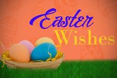 Imagen compuesta de los huevos de Pascua coloridos en cesta de mimbre Imágenes de archivo libres de regalías